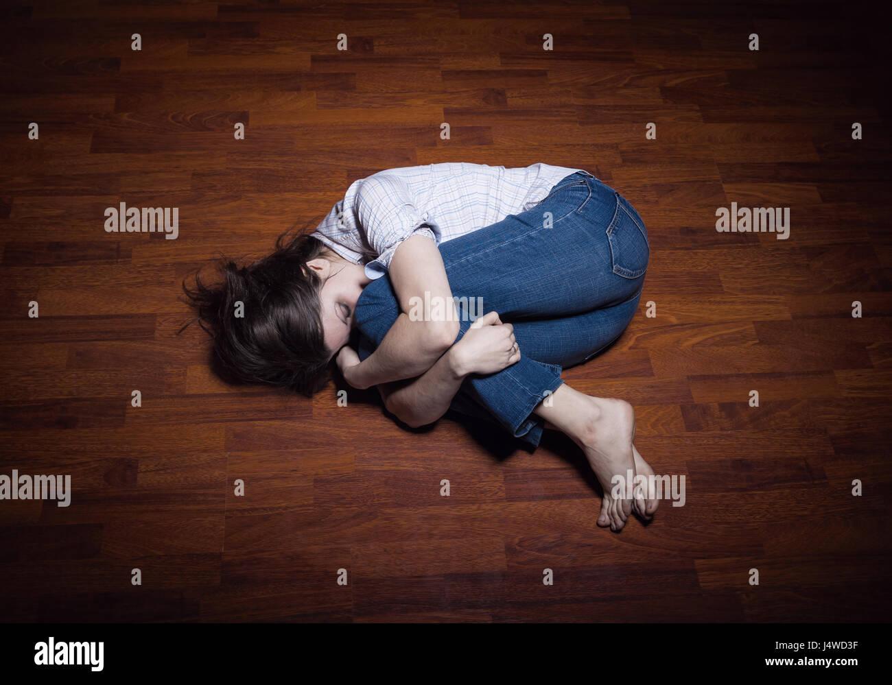Allongé sur le sol d'une jeune femme solitaire dans une chambre vide Photo Stock