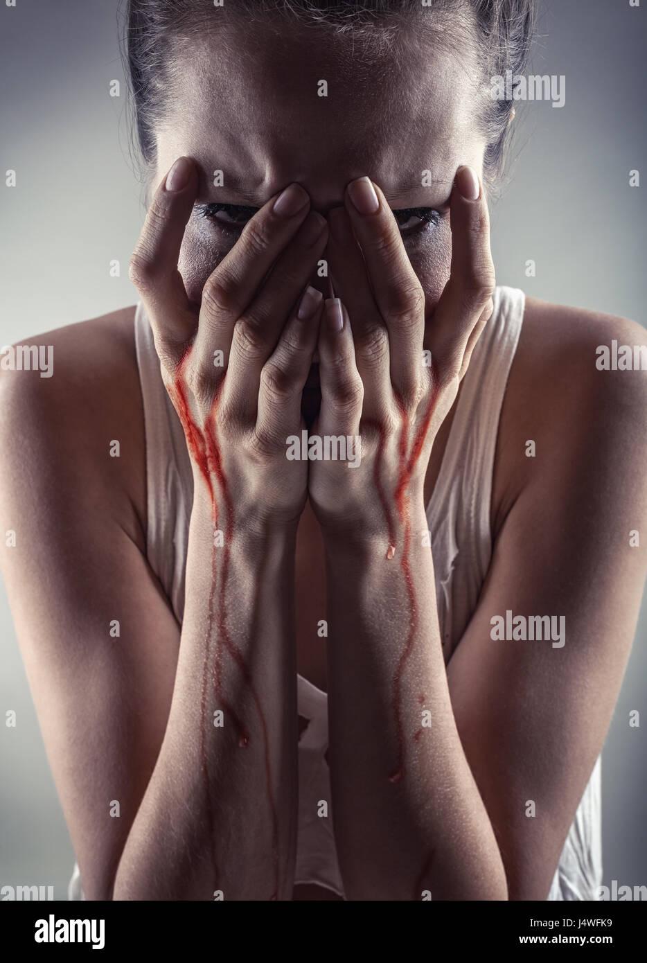 Femme pleurer avec ses mains dans le sang Photo Stock