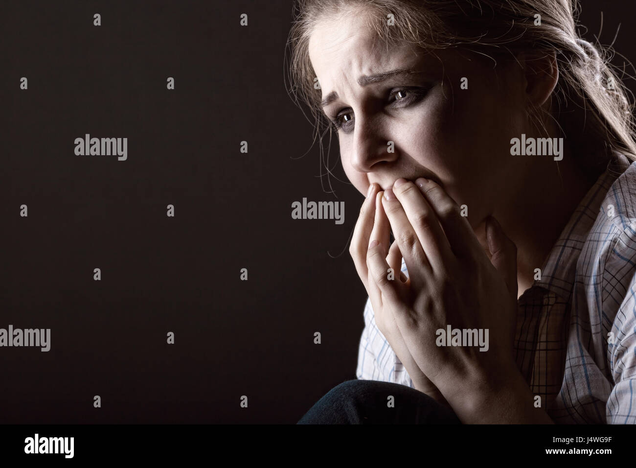 Jeune femme pleurer sur fond sombre Photo Stock