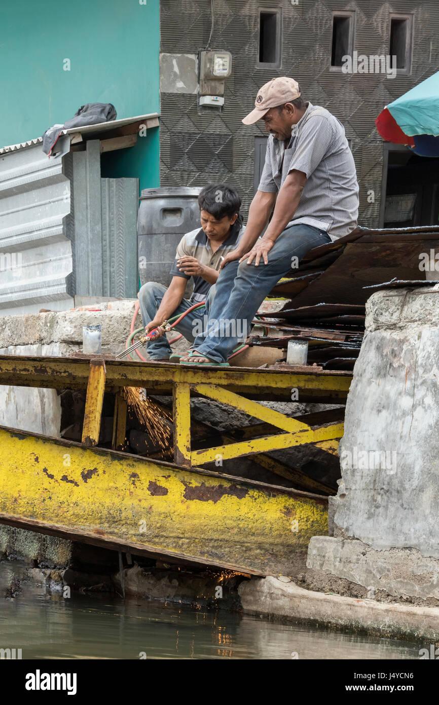Les soudeurs sur le pont jaune vertical, Sunda Kelapa port intérieur, Jakarta, Indonésie Photo Stock