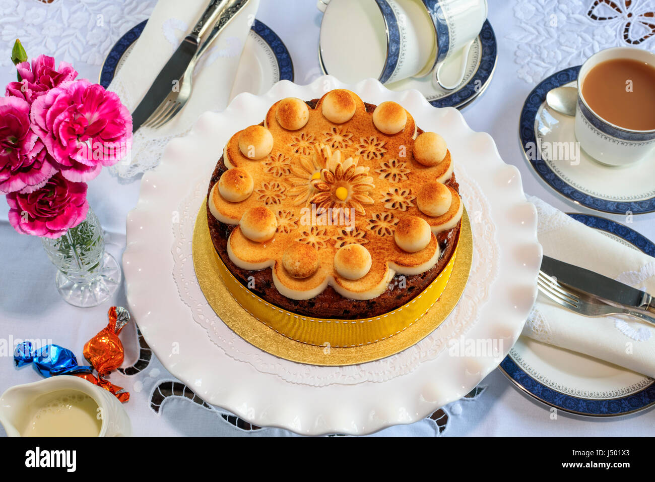 Simnel cake - gâteau aux fruits traditionnel de Pâques décorés de massepain sur un set de table Photo Stock