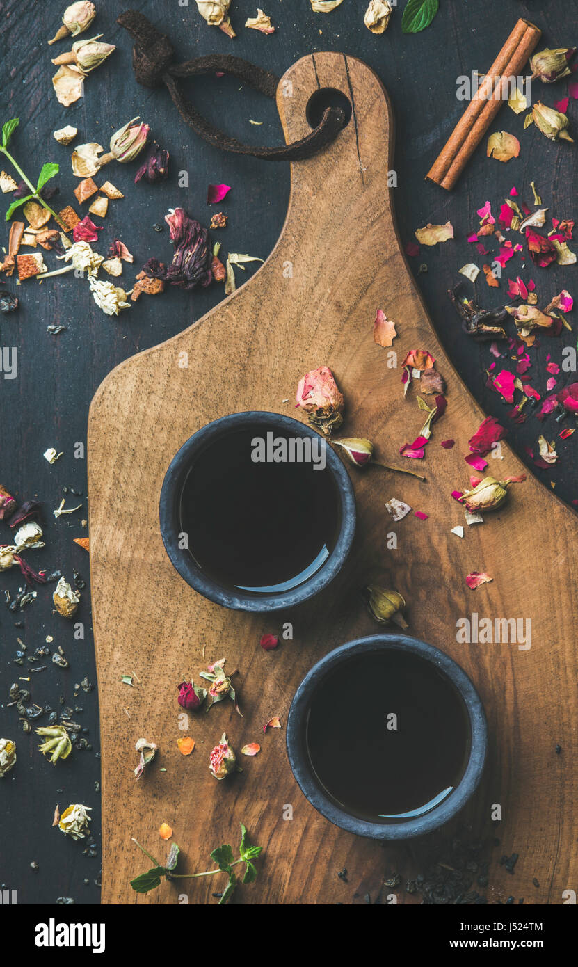 Thé noir chinois en grès noir tasses sur le service conseil en bois noir  sur fond de bois avec des herbes, des boutons de fleurs, de feuilles de thé  ... 1cb31f7d86e