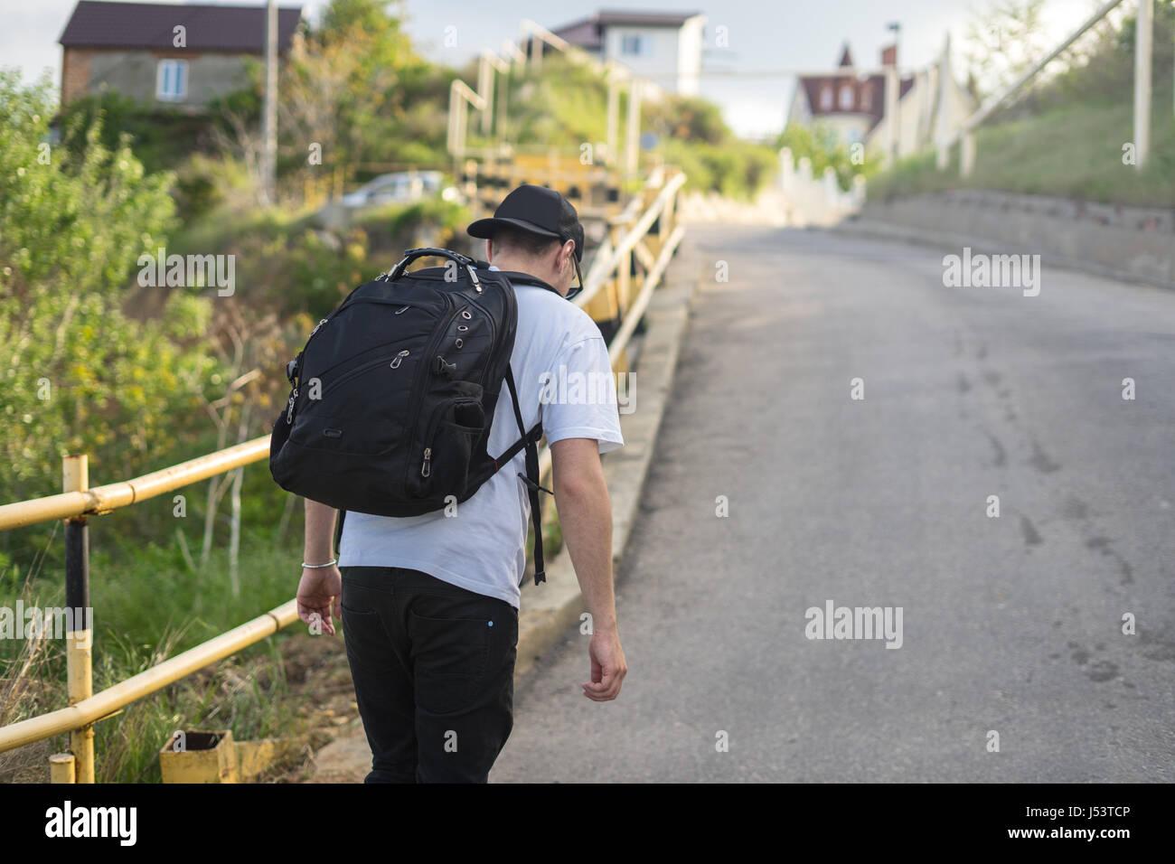 Jeune homme élégant avec un sac à dos marche seul sur une route de montagne Photo Stock
