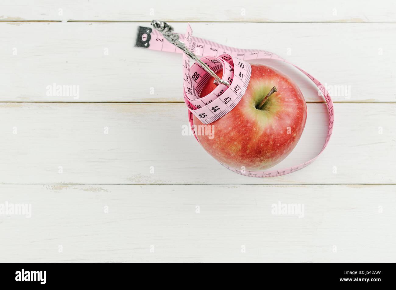 Pomme rouge avec un ruban à mesurer et la fourche sur fond de bois, l'alimentation concept Photo Stock