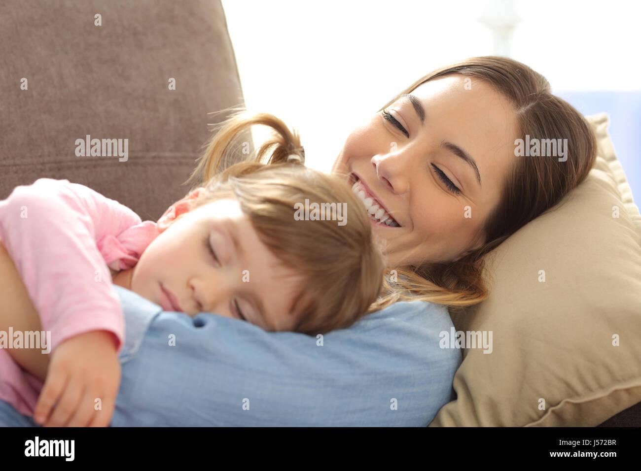 Gros plan d'une fière maman de regarder son bébé dormir couché sur un canapé dans la Photo Stock