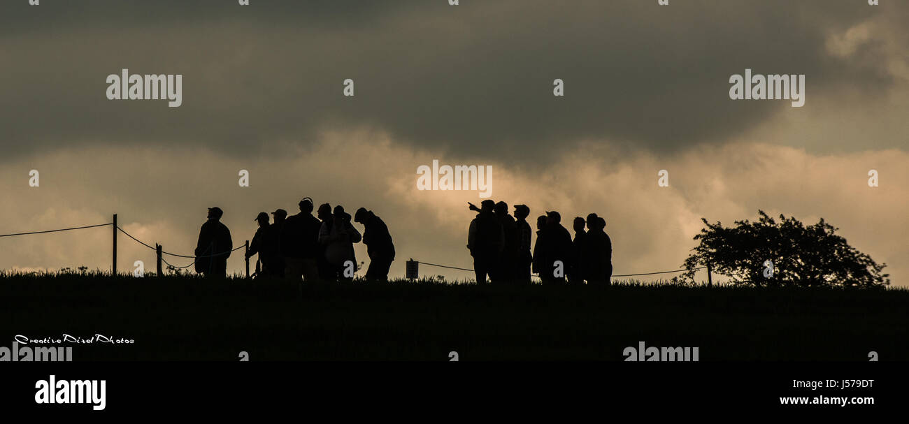 Silhouette de tir au pigeon d'argile concurrents en haut de colline avec ciel nuageux comme arrière-plan Photo Stock
