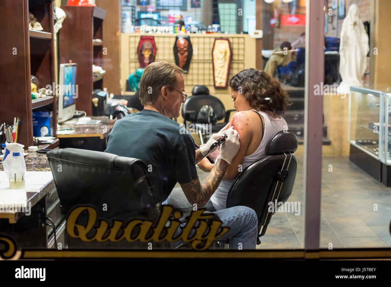 Tucson, Arizona - un artiste de tatouage au travail dans une boutique sur la 4e Avenue. Photo Stock