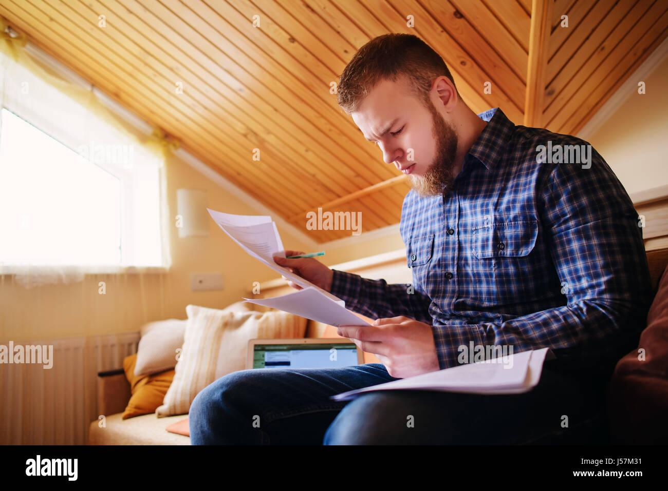 Jeune homme étudiant à la maison assis sur un canapé holding documents tout en travaillant sur un Photo Stock