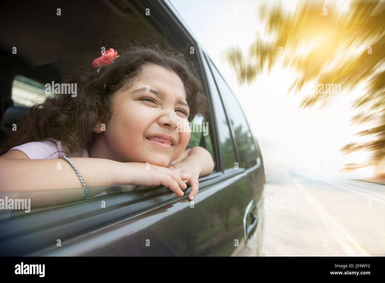 Smiling girl looking out car window Photo Stock