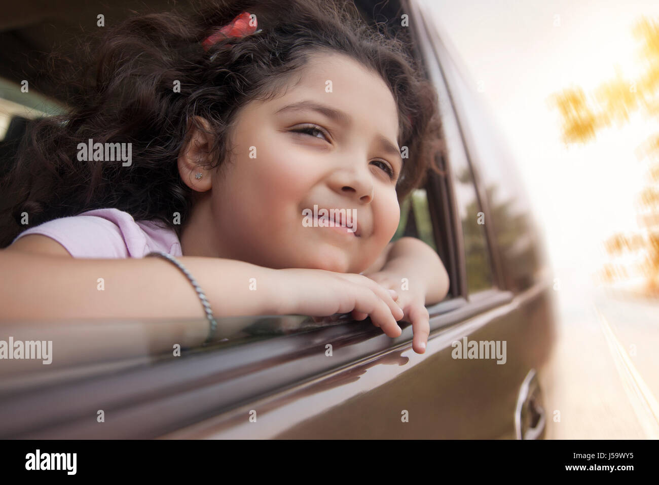 Girl looking out car window Photo Stock
