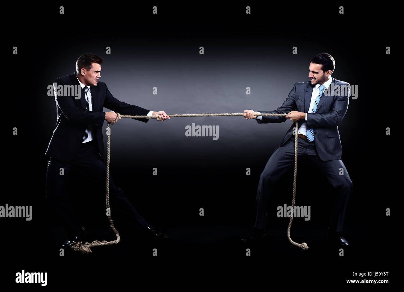 Deux hommes d'affaires en tirant la corde dans une compétition, isolé sur fond blanc Photo Stock