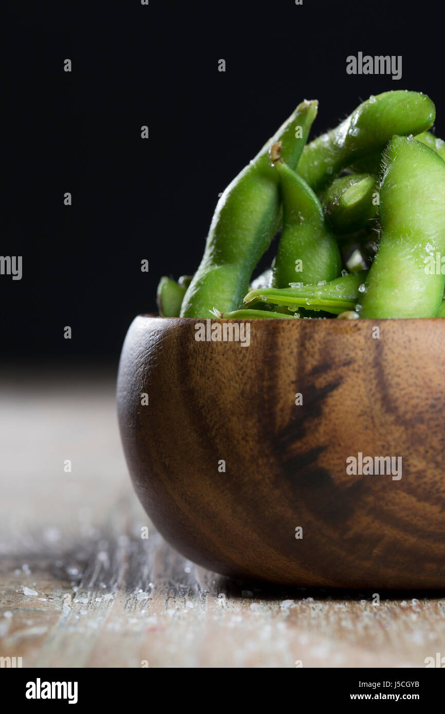 Bol d'edamame assis sur une table en bois rustique. Photo Stock