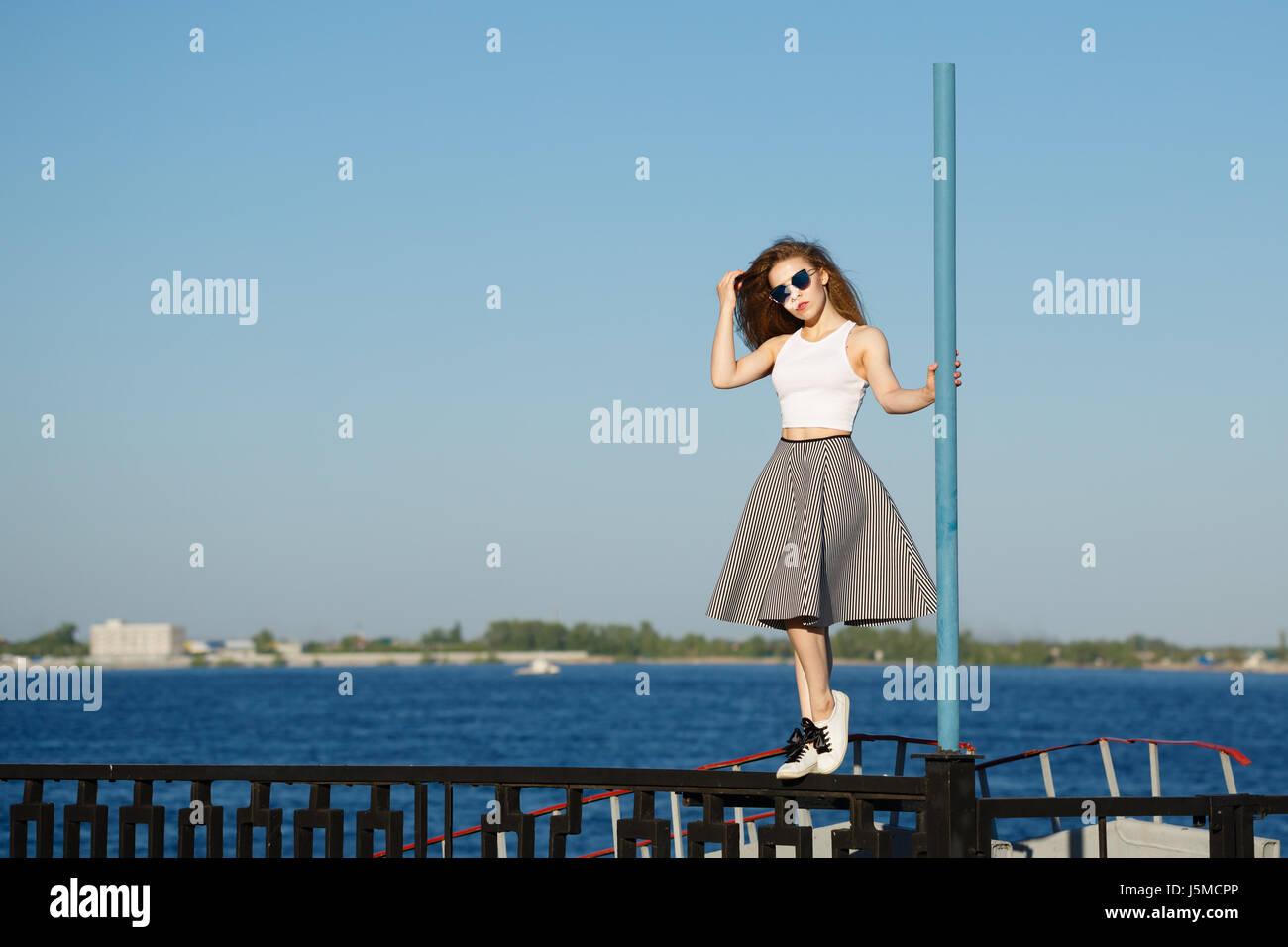 Jeune fille attirante hipster danser sur le poteau. Elle porte un top, une jupe et des lunettes. Le concept de la Photo Stock