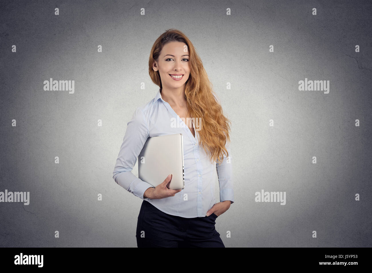 Portrait young beautiful happy woman holding laptop smiling standing bureau isolé sur fond de mur gris. Expression Photo Stock