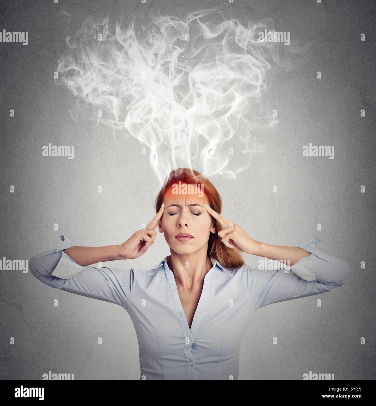 Portrait jeune femme penser trop dur vapeur s'échappant des chef isolé sur fond de mur gris. Perception Photo Stock