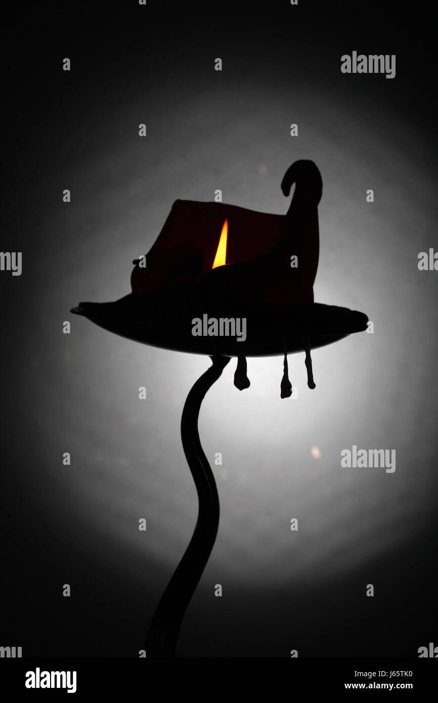 Une bougie brûlante curling noueux qui ressemble à un chapeau de sorcière / Haunted House ,avec trois gouttes de cire, suspendue au porte-bougie. Banque D'Images