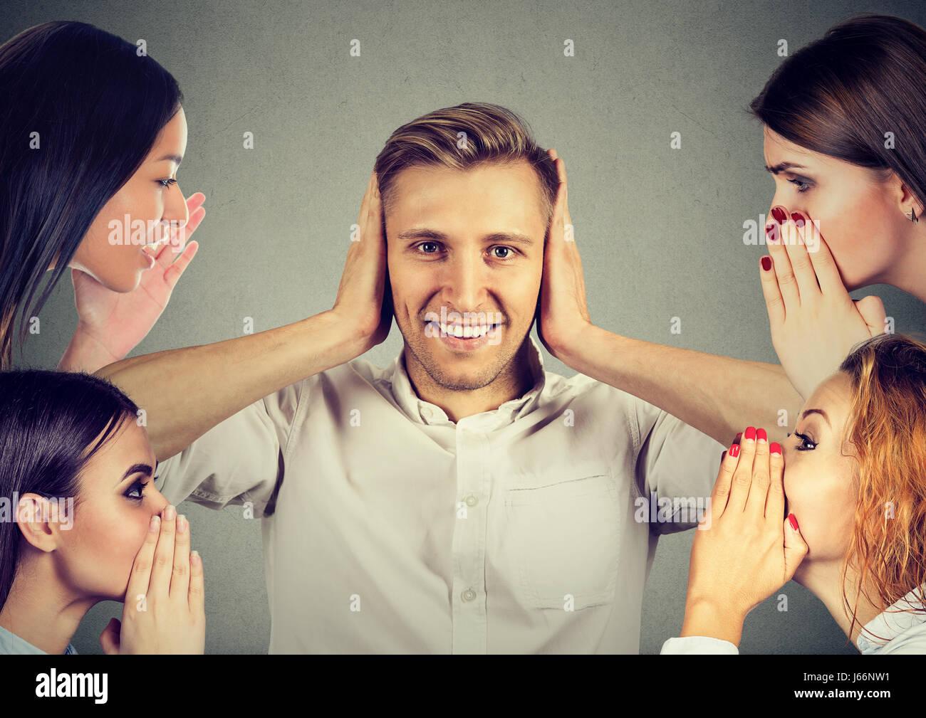 Quatre femmes whispering a secret les derniers potins à un jeune homme qui couvre les oreilles et ignorant Photo Stock
