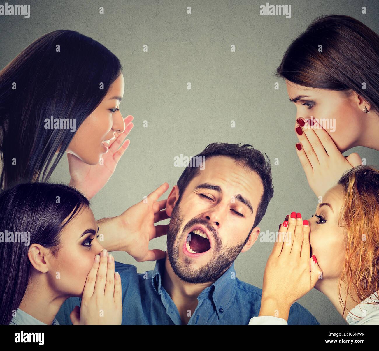Quatre femmes whispering a secret les derniers potins à un homme endormi s'ennuie Photo Stock