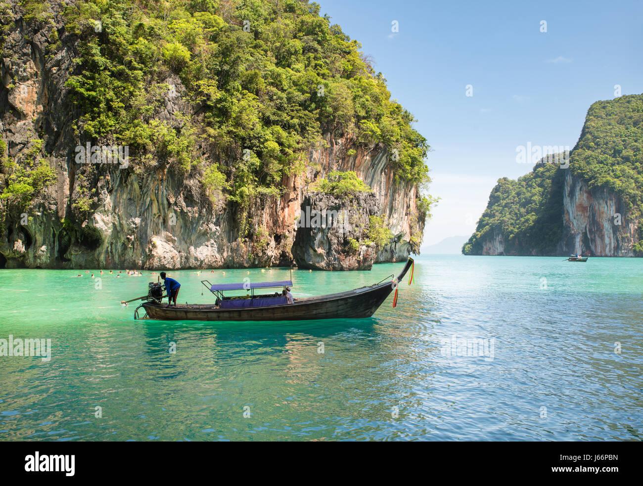 Magnifique paysage de montagne des roches et une mer cristalline avec bateau longtail à Phuket, Thailande. Photo Stock