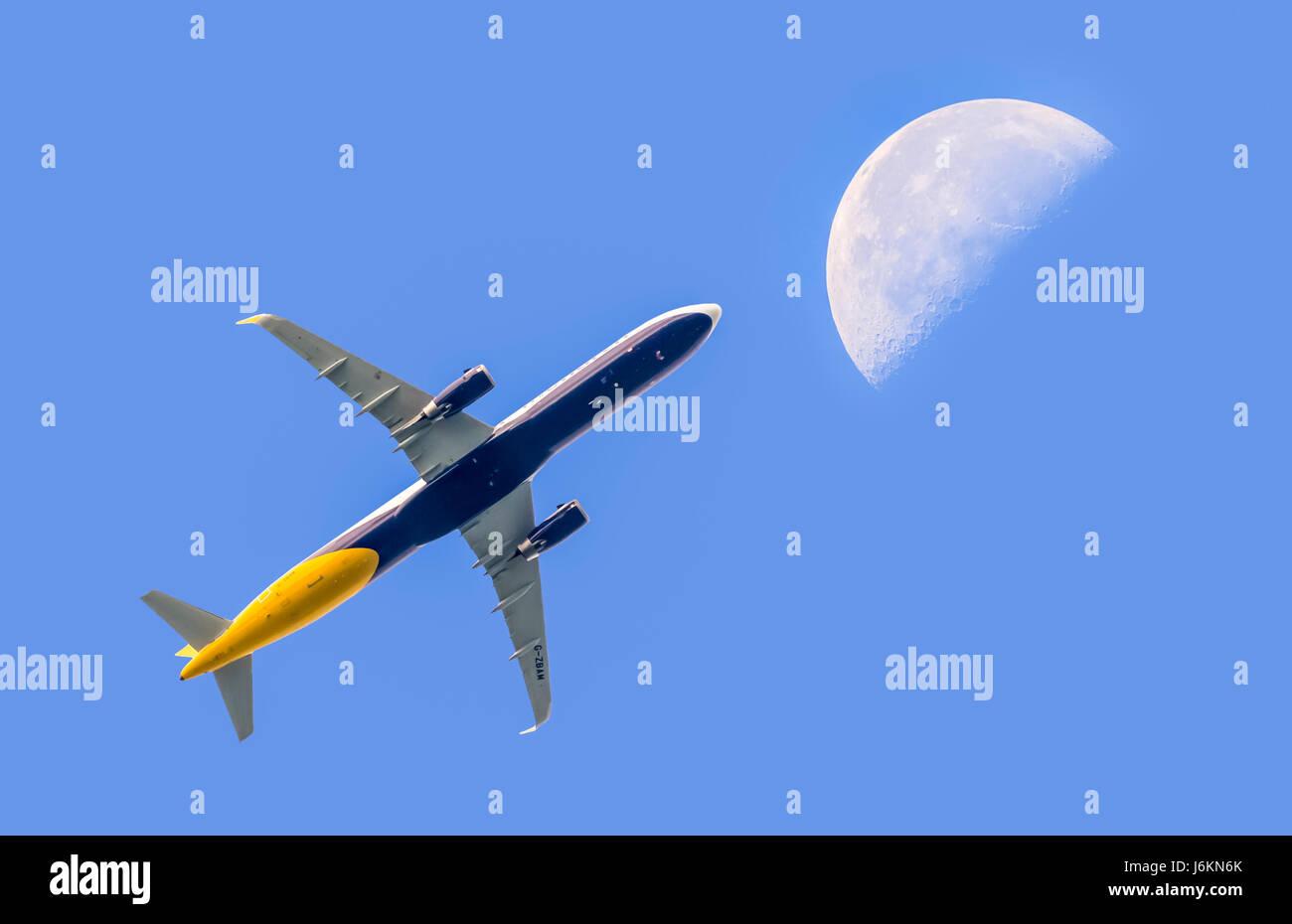Fly me to the moon. Passenger jet airplane flying high contre ciel bleu avec la lune au loin. Les voyages aériens. Photo Stock