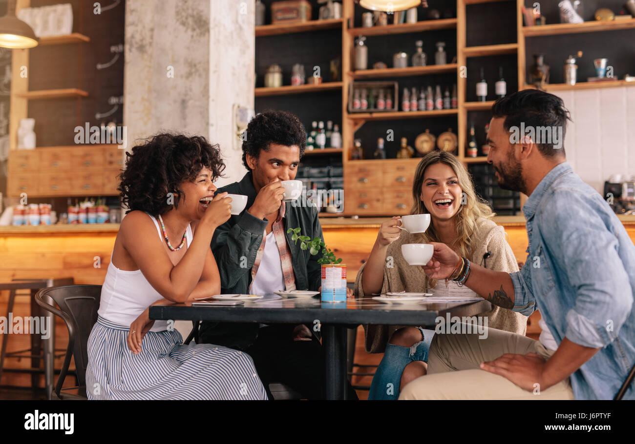 Groupe diversifié d'amis bénéficiant d'un café ensemble dans un restaurant et de parler. Les jeunes gens assis autour Banque D'Images