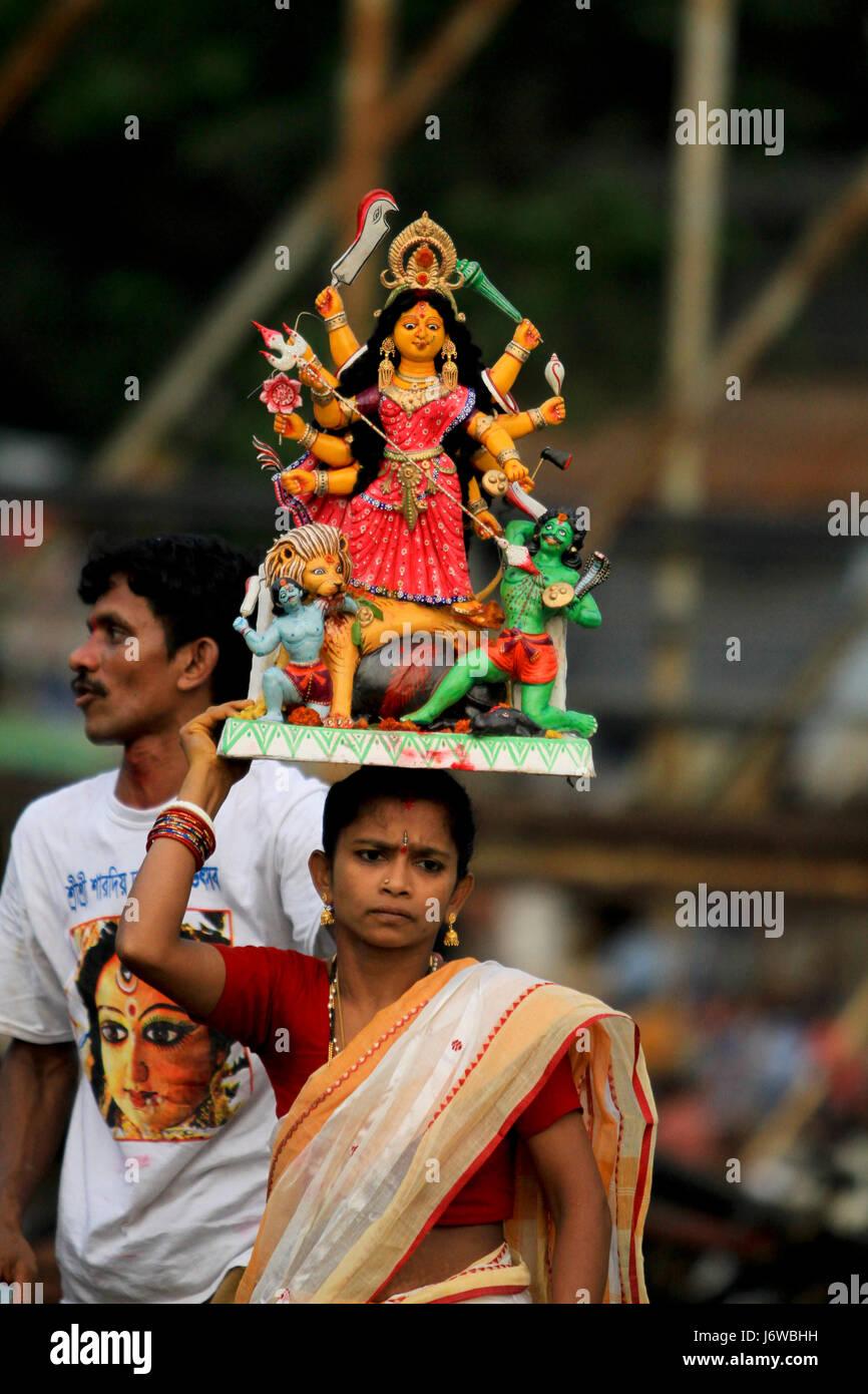 Un Hiindu dévot porte l'idole de la Déesse Durga à Bina Smriti Ghat près de Sadarghat de Photo Stock