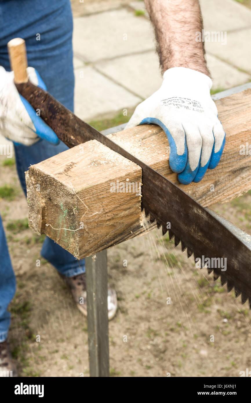 Morceau De Bois Brut un travailleur de la construction découpe une scie à main