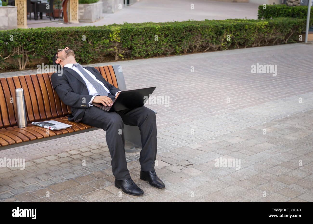 Businessman endormir onn un banc dans la Marina de Dubaï, Émirats arabes unis Photo Stock