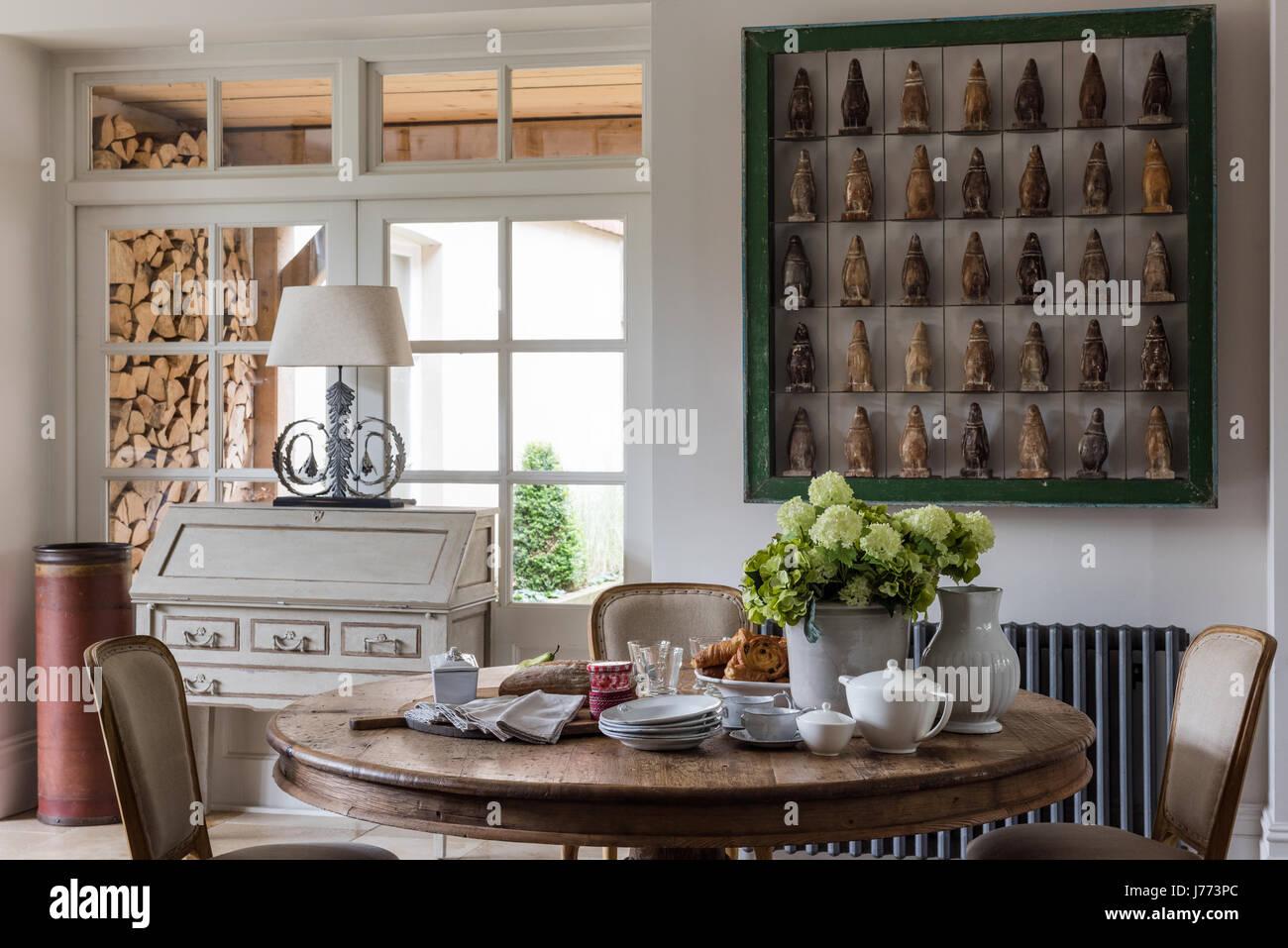 Penguin firgurines affiché dans un cadre vert gras sur le mur de cuisine. Le bureau, la lampe et la table circulaire Photo Stock