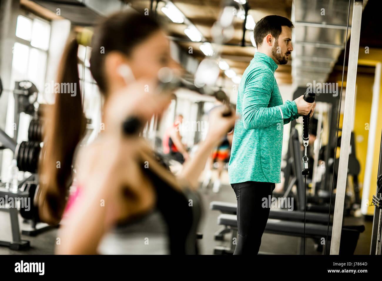 Exercices de musculation exercice Jeune couple dans la salle de sport moderne Photo Stock