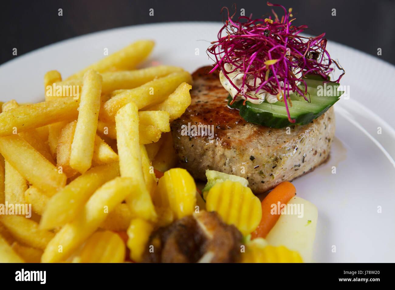 Escalope de porc servis avec frites et légumes à Interlaken en Suisse. Le beurre est garnie de fleurs Photo Stock