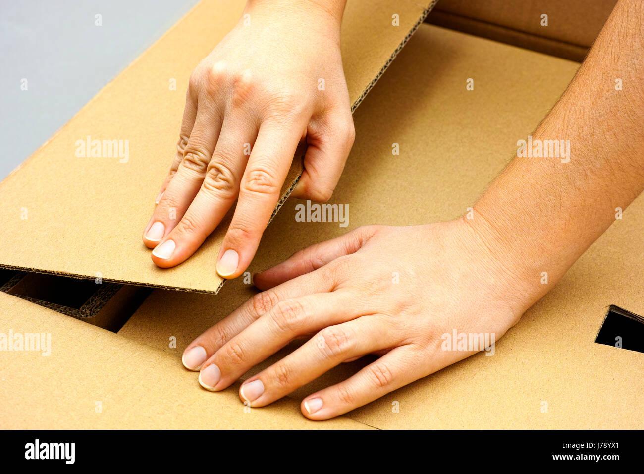Deux mains femme grande ouverture boîte en carton avec fond gris. Close-up. Photo Stock