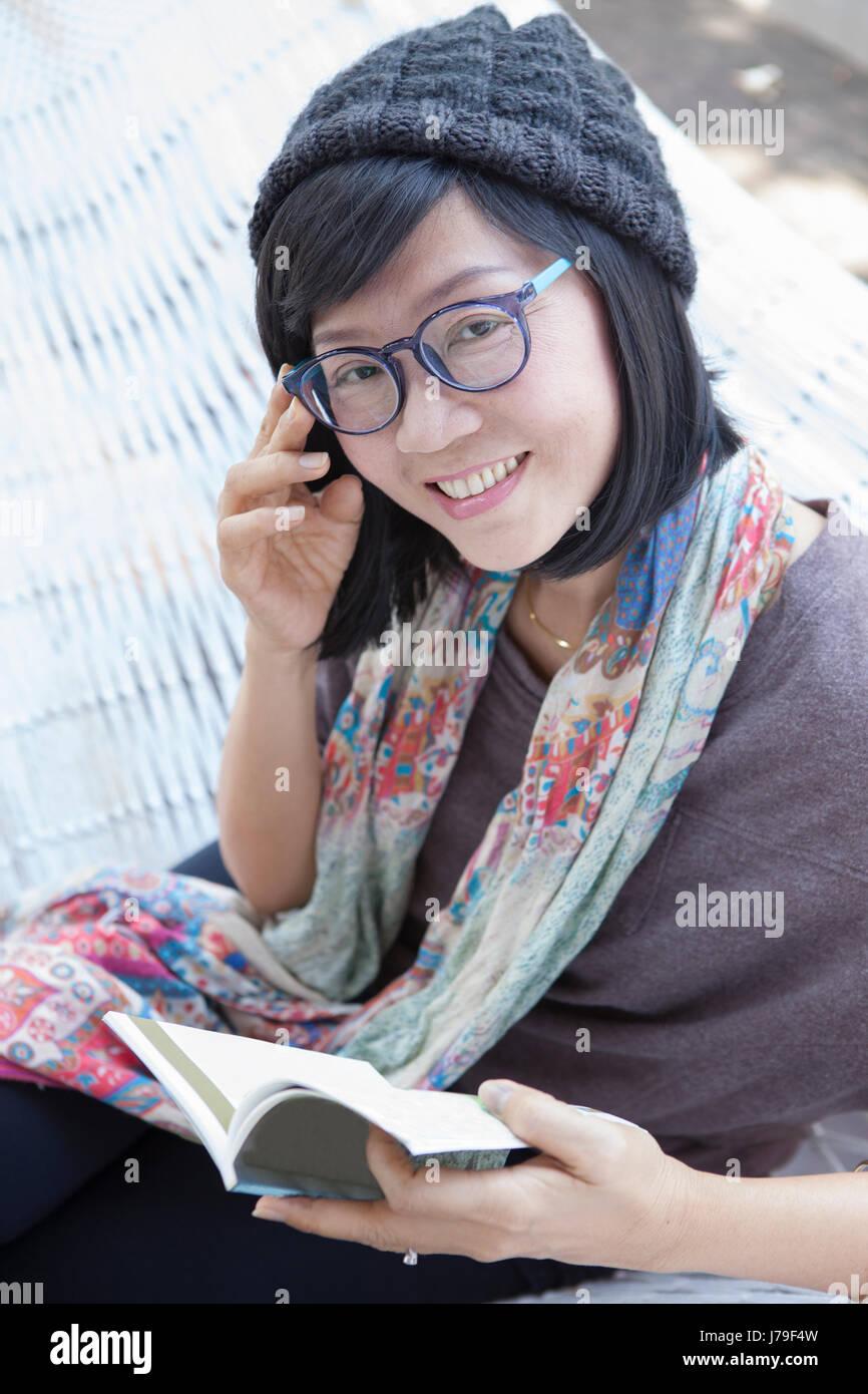 Femme Asiatique livre de poche et dans la main de détente sur station d'accueil Photo Stock