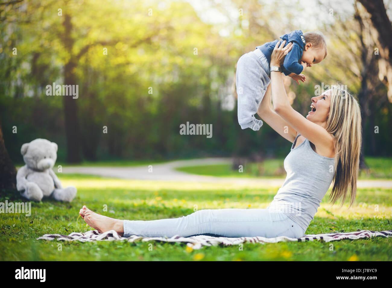 Heureuse mère avec son fils âgé d'un an à l'extérieur dans un parc Photo Stock