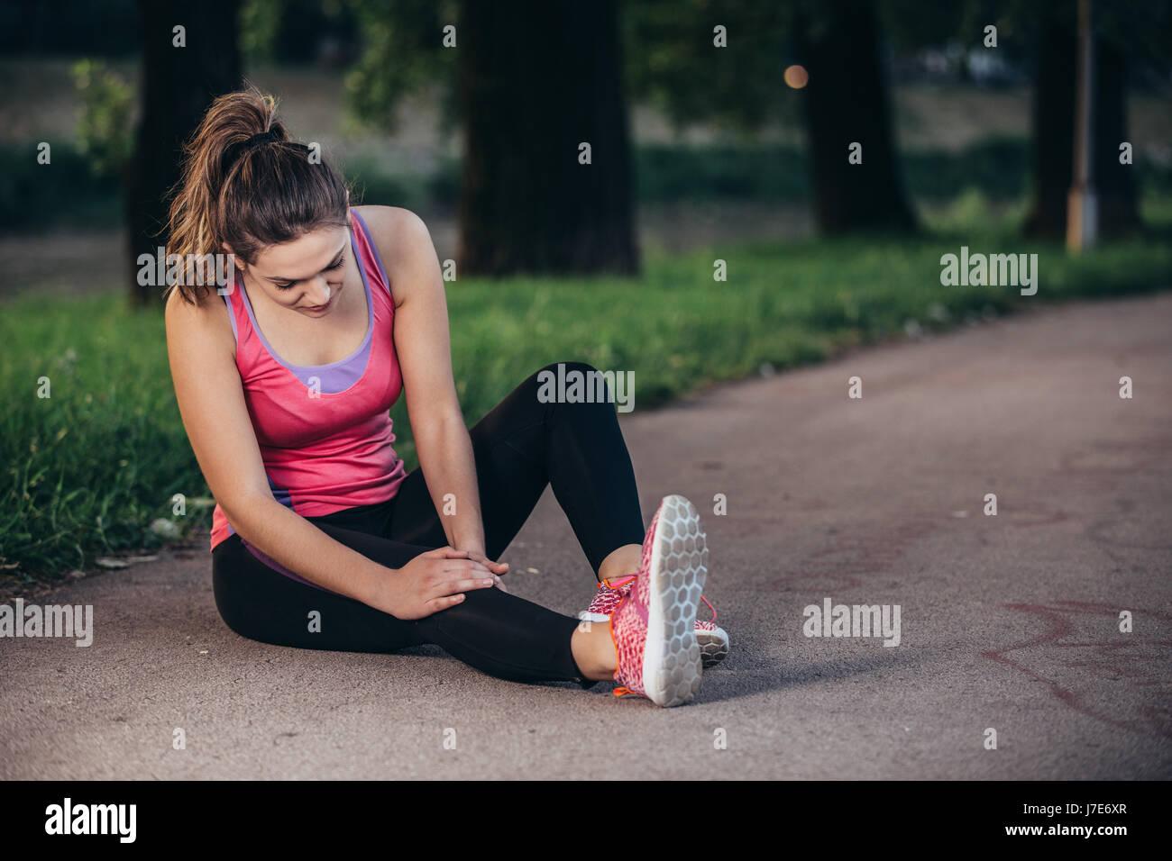Aide à l'homme femme avec genou blessé lors de l'activité sportive Photo Stock