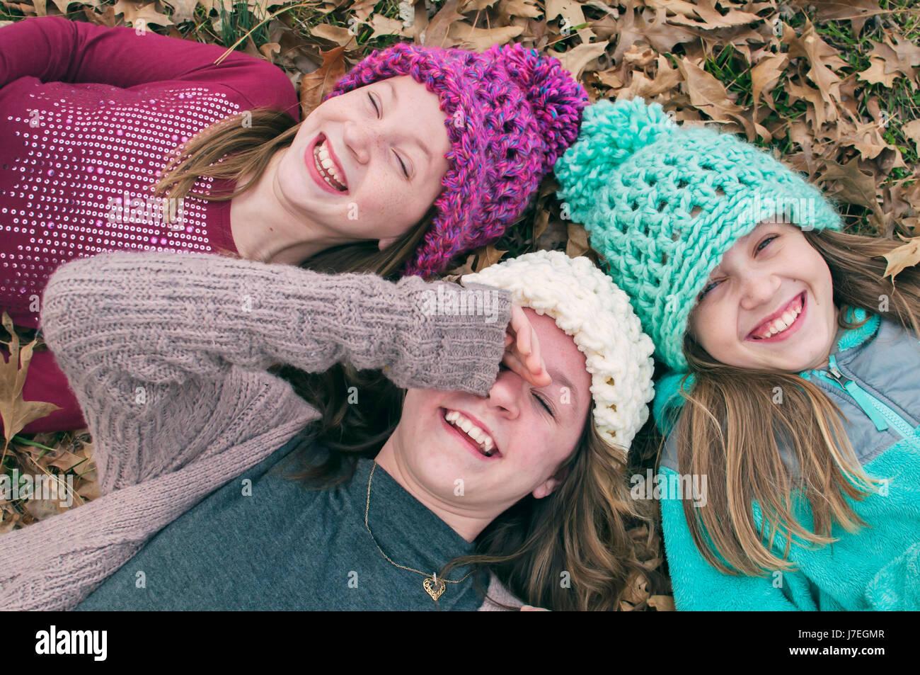 Trois jeunes filles riant port d'un chapeau Photo Stock