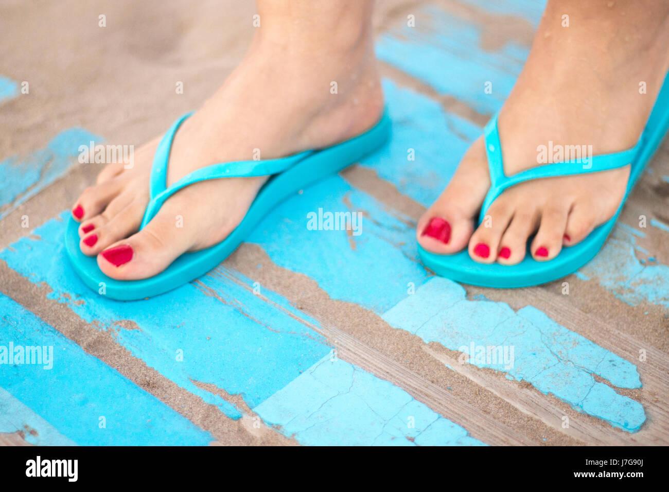 Lady's pieds avec du vernis à ongles rouge en sandales sur la plage de sable de l'océan en été sur passerelle en Banque D'Images