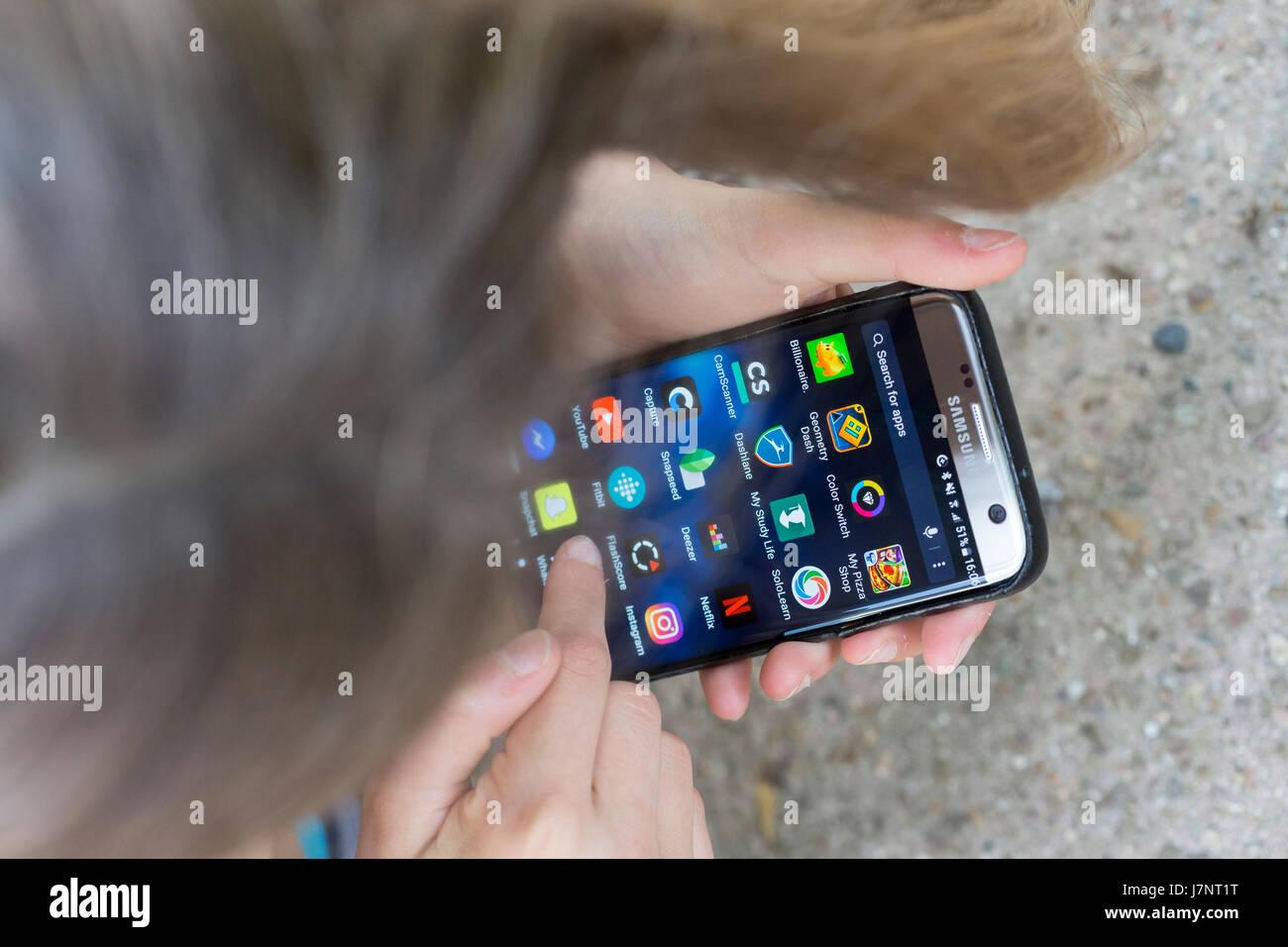 Une fille à l'aide d'écran tactile téléphone mobile / smartphone apps Photo Stock