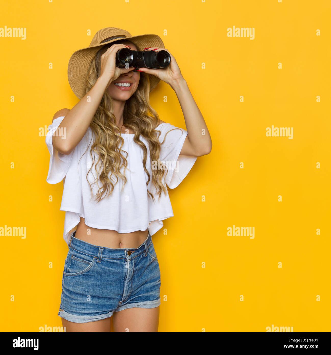 Jeune femme blonde en jeans pantalon, chemise blanche et chapeau de paille, à l'écart dans les jumelles, Photo Stock