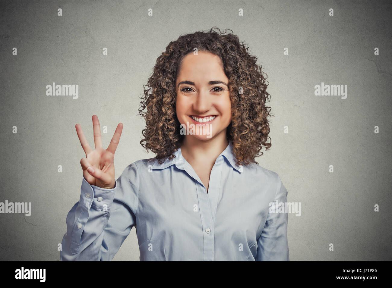 Closeup portrait jeune femme les cheveux bouclés en donnant trois doigts inscription mur gris isolé geste Photo Stock