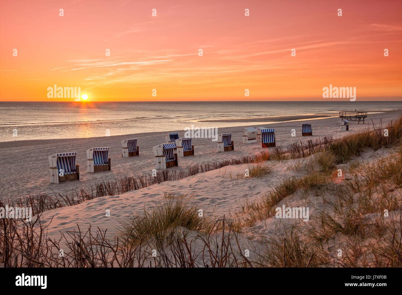 Chaises de plage à plage de la mer du Nord de Hörnum, Sylt, dans coucher du soleil Photo Stock