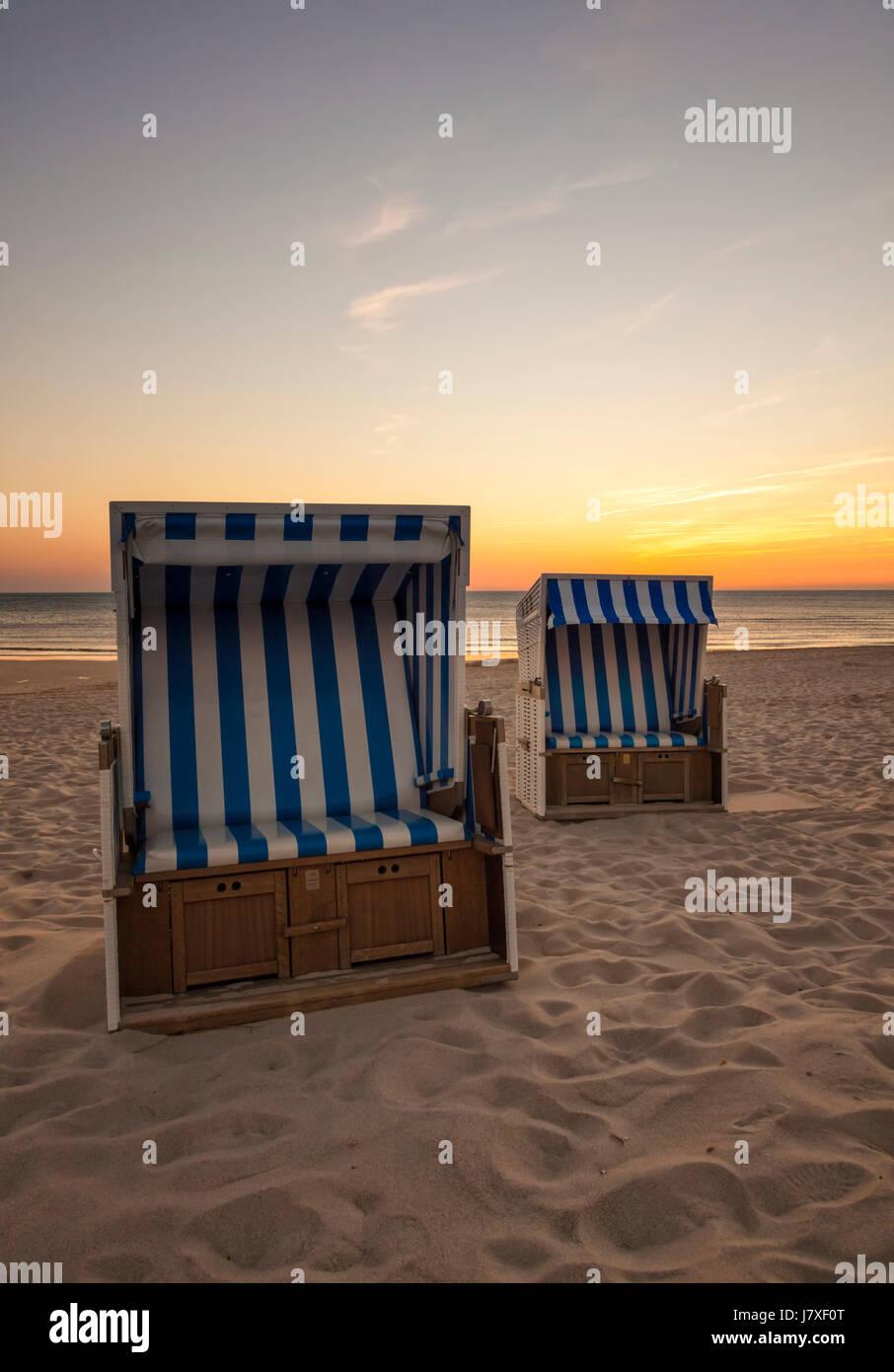 Deux chaises de plage à plage de la mer du Nord de Hornum, Sylt, dans coucher du soleil Photo Stock