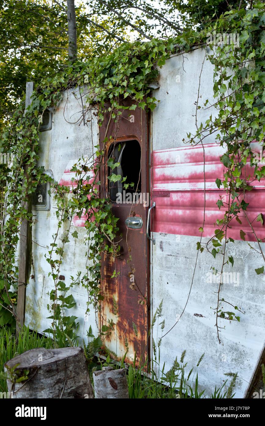 Vintage Travel Trailer Tour-A-Home, le repos sous les arbres de l'aulne, montre de nombreuses années d'utilisation, Banque D'Images