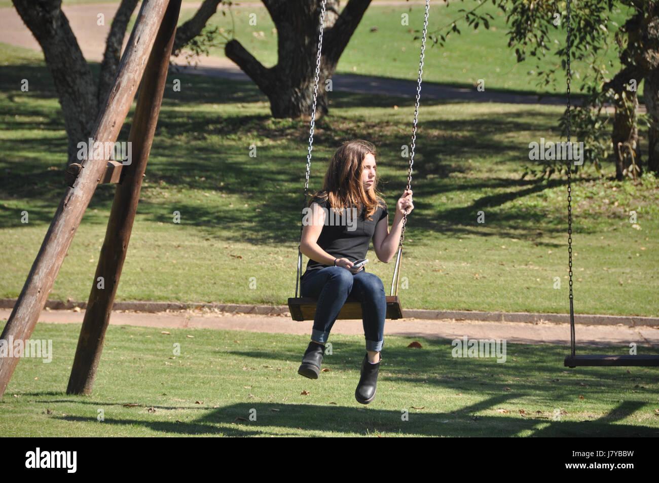 Jolie teen blonde en jeans et des manches courtes et des bottes est assis sur le bois et de rotation de la chaîne Photo Stock