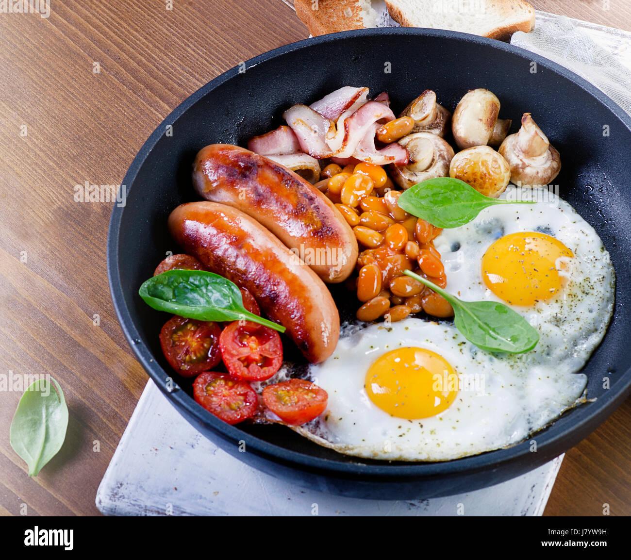 Le petit déjeuner anglais complet dans la casserole avec les œufs, saucisses, bacon, haricots, pain grillé, tomates Banque D'Images