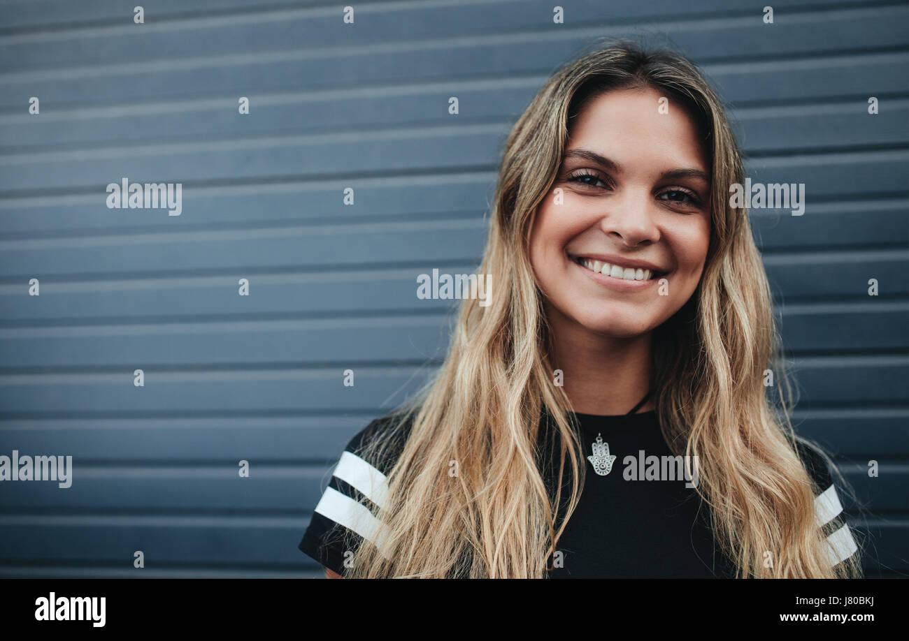 Close up portrait of smiling woman standing contre mur gris. Beau portrait jeune femme à la caméra et Photo Stock