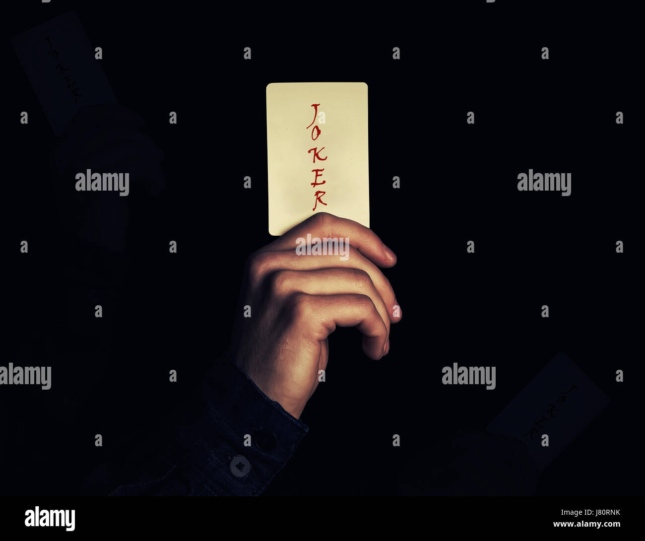 Close up of a man hand holding joker jeu de carte. Illusioniste montrant un tour de magie sur un fond noir. Jeu Photo Stock