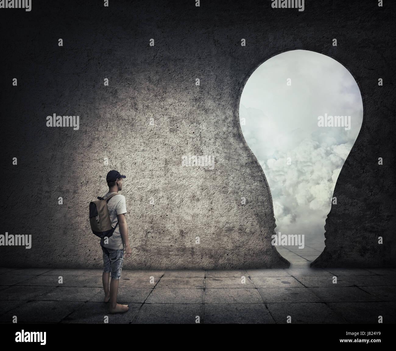 Image conceptuelle avec une personne debout dans une pièce sombre, en face d'une porte en forme d'ampoule. Photo Stock