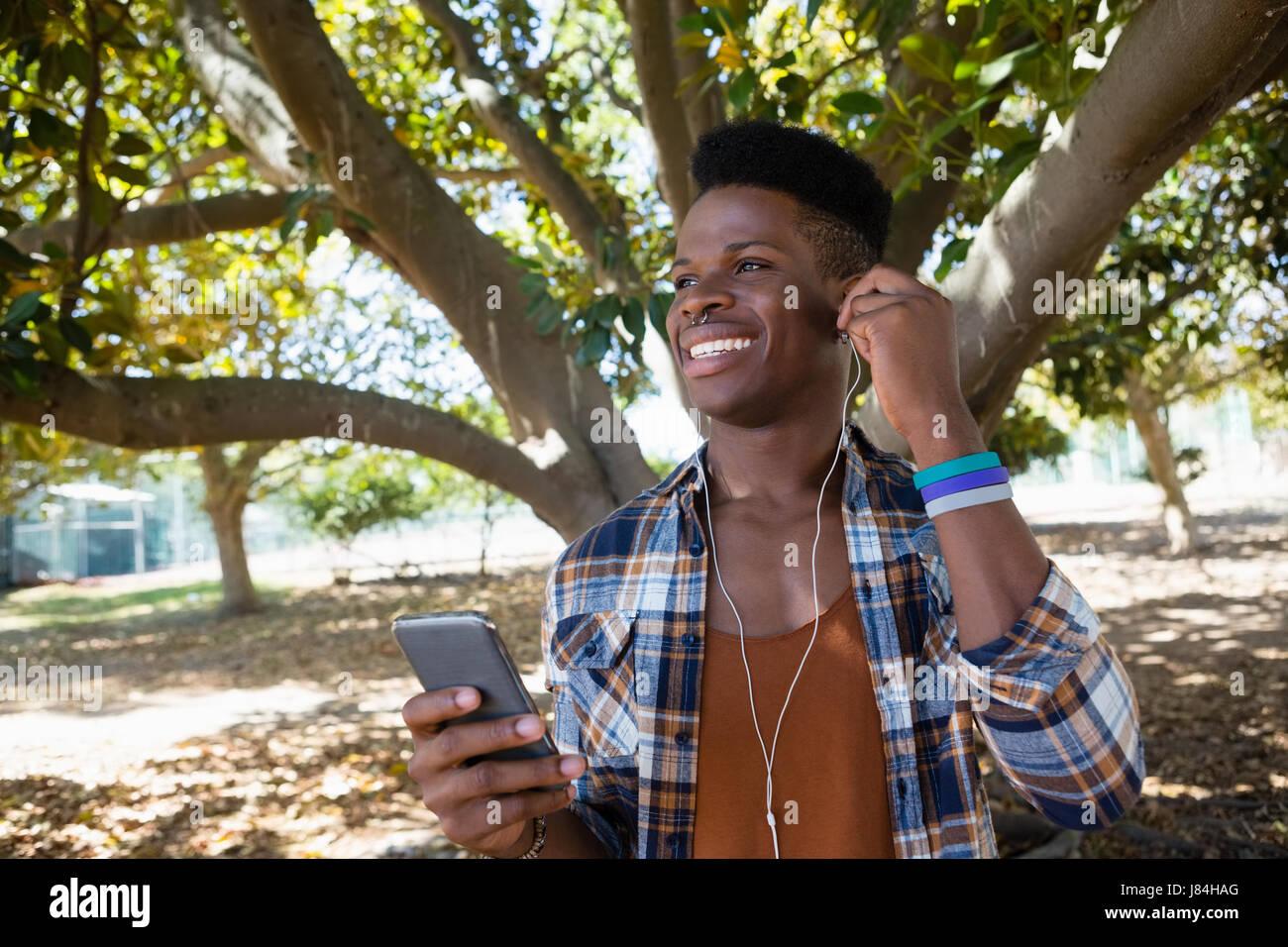 Jeune homme avec vos écouteurs à écouter de la musique sur téléphone mobile dans le parc Banque D'Images