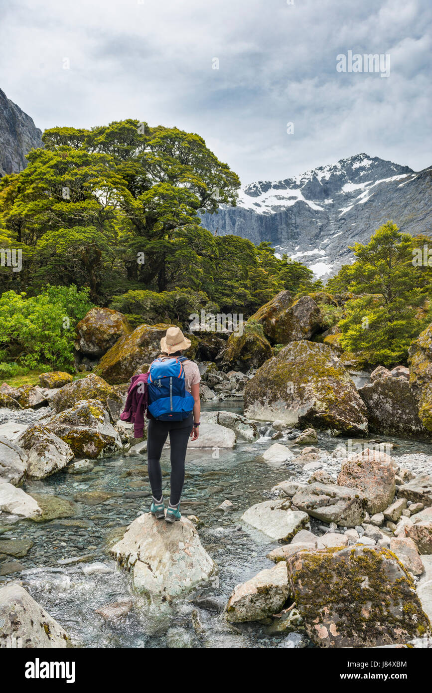 Female hiker sur un rocher dans la rivière, le Parc National de Fiordland, Southland, Nouvelle-Zélande Photo Stock